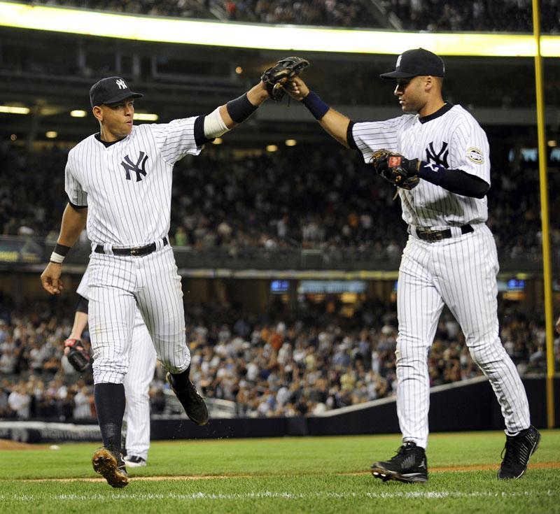 New York Yankees third baseman Alex Rodriguez high-fives shortstop Derek Jeter in Bronx, New York, Monday, September 13, 2009. Photo Credit: Kathy Kmonicek / MCT