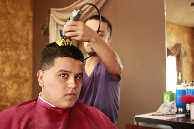 Romo  cuts Richard Lepe's hair at his barber shop. Lepe has been a loyal customer since the shop opened up seven months ago.