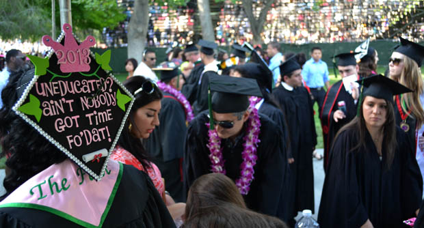 The College of Health and Human Development students gathered on the Oviatt Lawn minutes before taking their seats for their commencement ceremony.  Many graduates customized their caps to fit their personalities and while doing so they made sure that they were easily spotted from a distance.  Photo credit: John Saringo-Rodriguez / Photo Editor