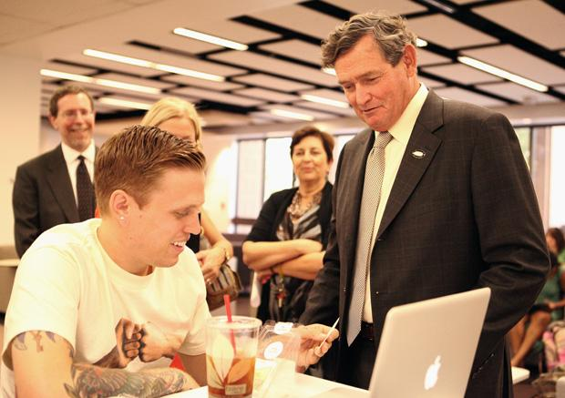 CSU Chancellor Timothy White gives Robert Querfurth, 23, a business marketing major his card after introducing himself in the Oviatt Library during his campus tour. Photo credit: Loren Townsley/ Editor in Chief