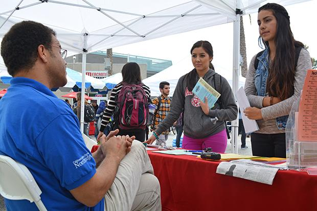 """Lindsay Ibarra (Left), 20, a public health promotion major and Roxanna Peza (Right), 20, a biology major, speak to University Counseling Services. """"I had questions about when the Blues Project would be recruiting. I want to help spread awareness and contribute to CSUN and show Matador pride."""" Hundreds of students visited the fair for 'Beat the Blues' week hosted by the Blues Project on Tuesday. Photo credit: John Saringo-Rodriguez / Photo Editor"""