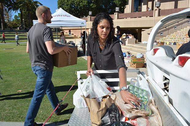 """Community Engagement's service learning coordinator, Nicole Linton, helps unpack donated goods for the clothing and food drive event. """"This is my first time...It's really great to see the outcome,"""" Linton said. Photo credit: John Saringo-Rodriguez / Photo Editor"""