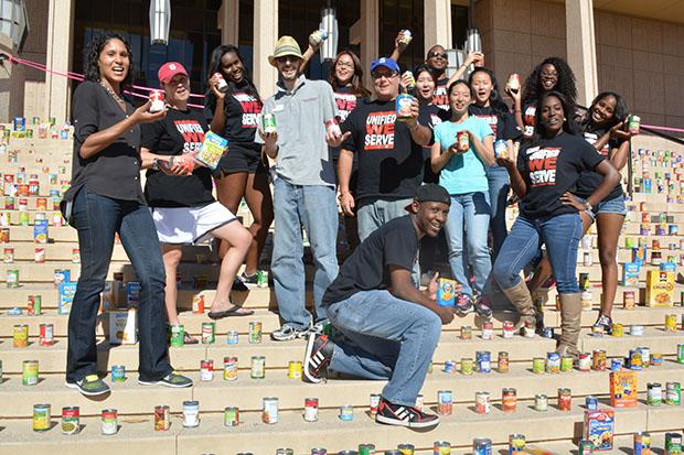 Unified We Serve (UWS) and Community Engagement volunteers stand amidst the 9,013 non-perishable goods raised at their annual clothing and canned food drive. They collected goods from CSUN students, staff and faculty for two weeks. Photo credit: John Saringo-Rodriguez / Photo Editor