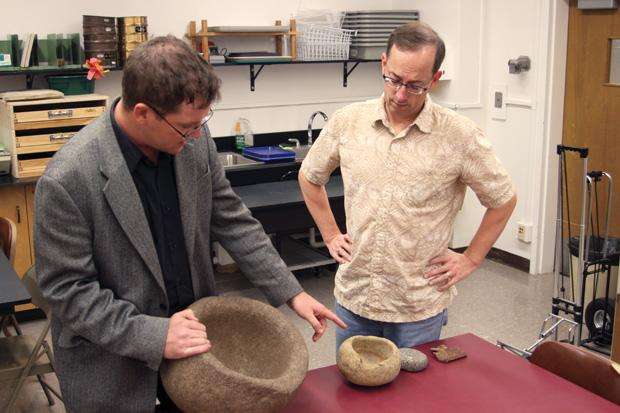 Dr. James Snead, director of the Anthropological Research Institute and archeology professor, reveals to Dr. Matthew Des Lauriers, fellow anthropology colleague, a fragment of equipment from the 1928 St. Francis Dam Disaster. Photo Credit: Andrea Alexanian