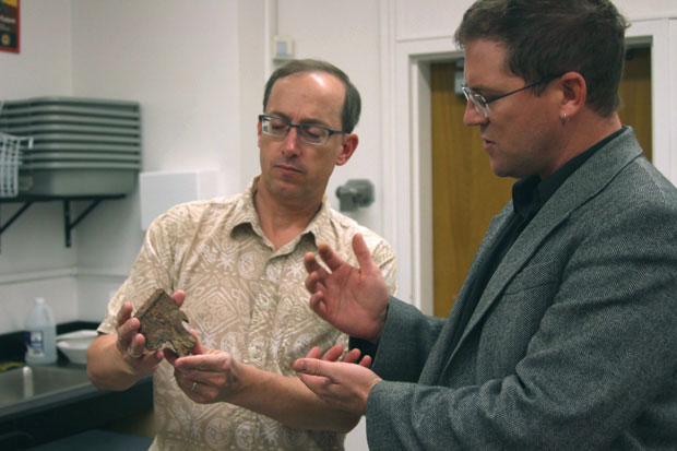 Dr. James Smead, director of the Anthropological Research Institute and archeology professor, reveals to Dr. Matthew Des Lauriers, fellow anthropology colleague, a fragment of equipment from the 1928 St. Francis Dam Disaster. Photo Credit: Andrea Alexanian