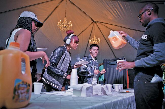 Sociology major, Steven Hall, serves orange juice to students picking up free pancakes during Final Flip on Wednesday. (Photo Credit: Charlie Kaijo / Senior Photogrpaher)