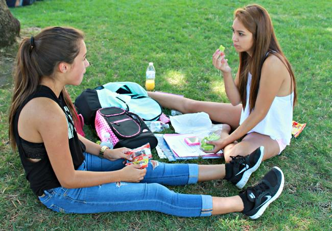 Ashley Rivera, 17, Communications Major and Alejandra Medina, 18, Communications Major enjoy healthy snacks of apples and cucumbers during their lunch breaks outside of Sierra Hall.  Demi Corso/Sundial Staff