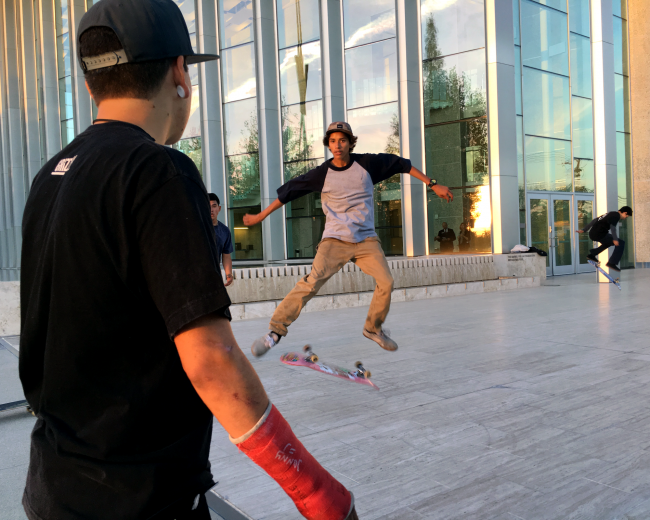 Rick Molina, from Northridge, watches his friend Mauricio Arana, from Granada Hills, perform a hardflip in front of the VPAC Wednesday evening. (Patricia Perdomo / The Sundial)