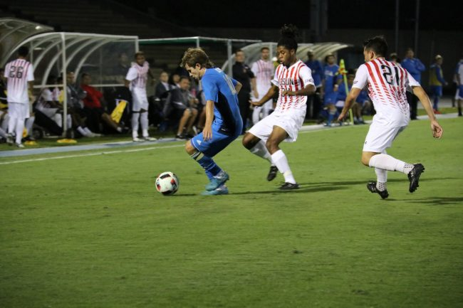 Sophomore Dre Deas, left, and Senior Richard Martinez, right, team up against UCLA to get the ball. Photo Credit: Kendall Faulkner