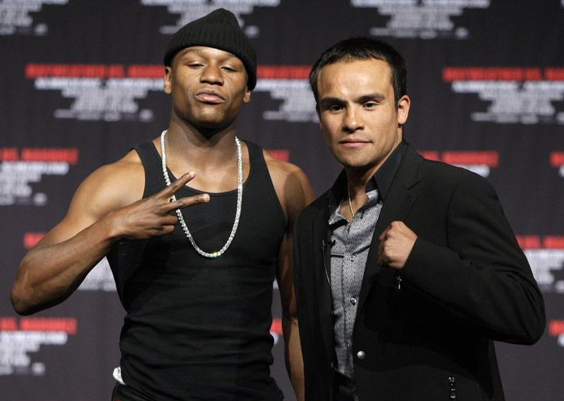 Boxers Juan Manuel Marquez, right, of Mexico, and Floyd Mayweather Jr. face off during a news conference at the MGM Grand in Las Vegas, Saturday, May 2, 2009. Mayweather formally announced his return to boxing Saturday, less than a year after he retired and said he was through with the sport. The two will fight on July 18 in a fight with a 143-pound limit. Photo Credit: Jae C. Hong / AP Photo