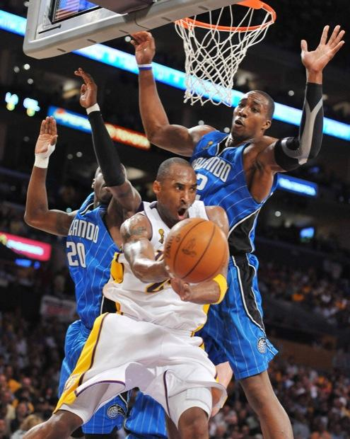 The Los Angeles Lakers' Kobe Bryant passes the ball in front of the Orlando Magic's Dwight Howard and Mickael Pietrus during second half action in Game 2 of the NBA Finals at the Staples Center in Los Angeles, California, Sunday, June 7, 2009. (Michael Goulding/Orange County Register/MCT)