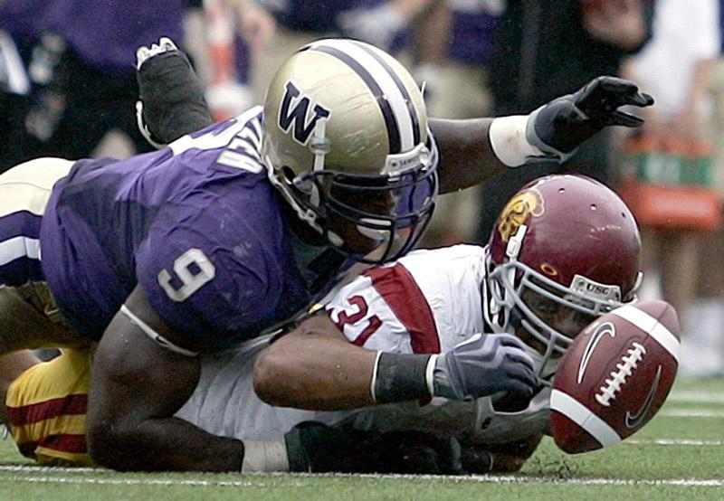 Washington's Donald Butler, left, fights for a fumble against Souther California's Stanley Havili. The Huskies gave the Trojans their first defeat of the season, putting the men of Troy in 0-1 hole in Pac 10 play. Photo Credi: John Lok/ MCT