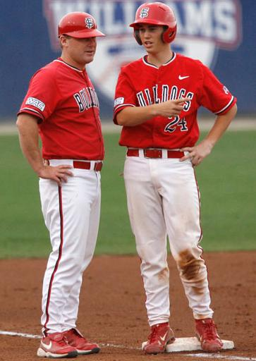 Matt Curtis (left), a former assistant coach at Fresno State, consults a team member at third base. Photo Credit: Courtesy of CSUN Media Athletics