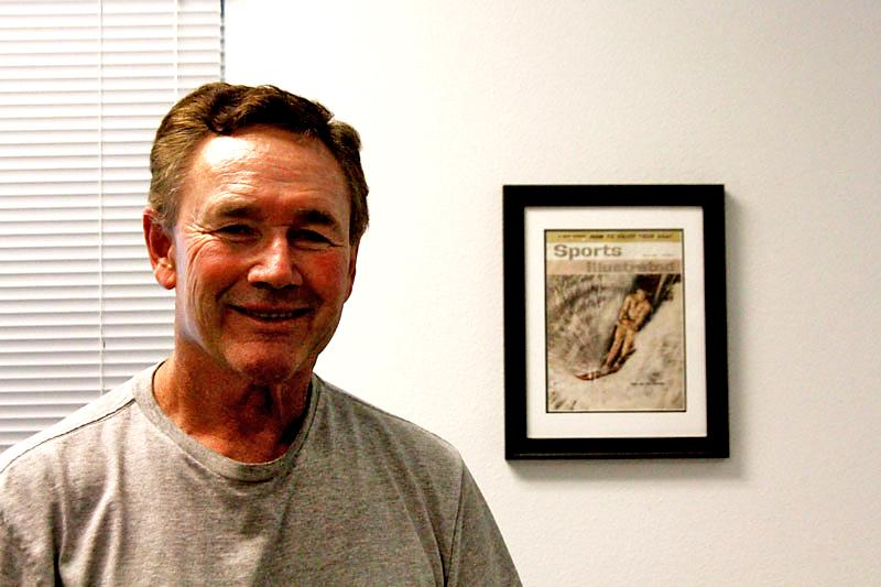Coach Van Arsdale stands next to a copy of the Sports Illustrated (SI) magazine cover that is framed on his office wall.  Coach Van Arsdale was the first waterskiier to grace the covers of SI. Photo Credit: Paul Kingsley/ Photo Editor