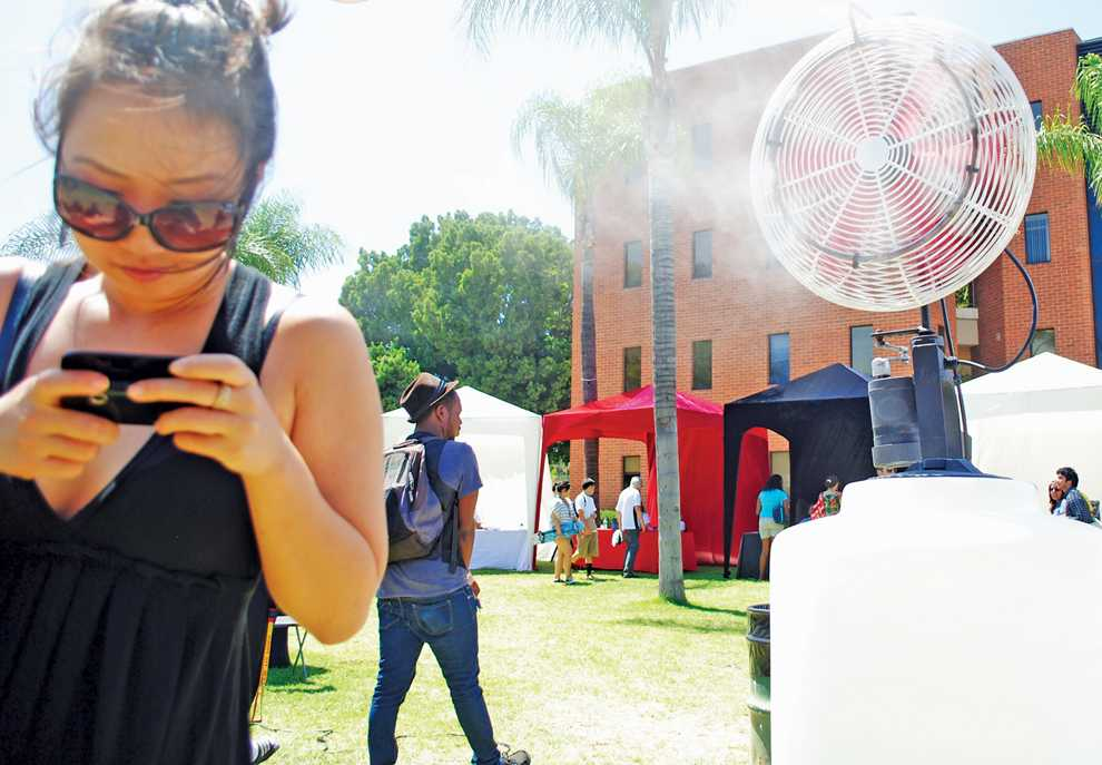 Grace Dong, enviromental occupational health major, tries to keep cool by the mist fan at the A.S. Fair on the second day of classes on Tuesday. Photo Credit: Andres Aguila / Daily Sundial