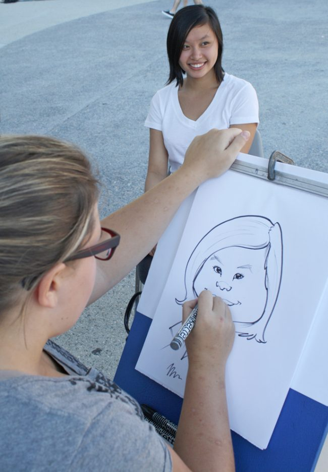Diana Lin, 21, accounting major sits for Kelcie Gruenberg who has been drawing caricatures for nine years. Students were given the opportunity to be drawn for free during the Hawaiian themed Matafest at the USU on Wednesday. Photo Credit: Mariela Molina / Visual Editor