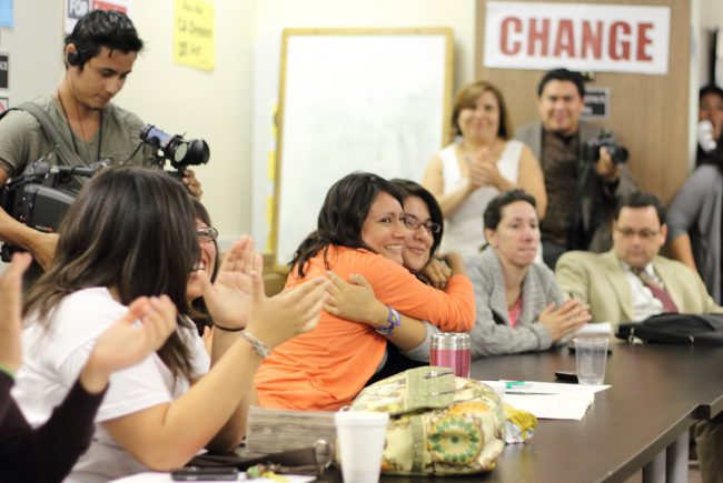 It passed: Helena Villa and Mirna Ortiz hug to celebrate the passing of AB 131 at the Coalition for Humane Immigrant Rights of Los Angeles on Friday. Photo Credit: Simon Gambaryan / Daily Sundial