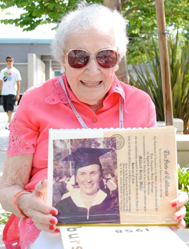 Mildred Wells, 99, holds up a photograph of herself in her cap and gown. She was part of the first graduating class at CSUN in 1958. Matthew Rubinfeld / Contributor