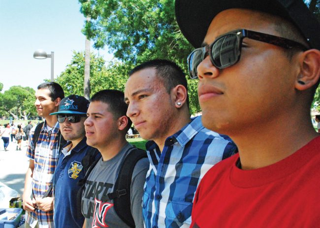 The Hermanos Unidos de CSUN stand in front of their booth on the first day of class, helping lost students find their way around CSUN.
