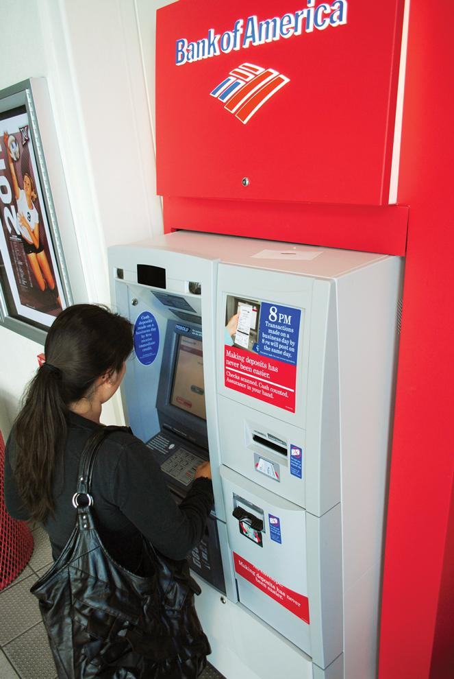 Maria Vasquez, sociology freshman major, 18, gets money out of a Bank of America atm machine in the Matador Bookstore Complex. Bank of America might start charging debit-card users five dollars a month when using their cards to purchase items.
