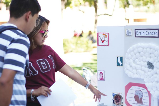 Jennifer Yessi of the Lambda Theta Alpha Sorority talks to a student about brain cancer and tumors during the Greeks Against Cancer event. Simon Gambaryan / Daily Sundial