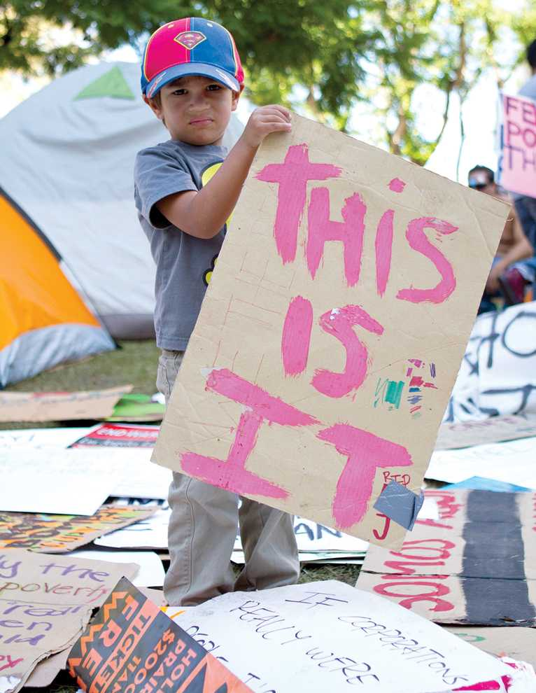 A little boy chooses a sign from a pile of protest signs on City Hall's north lawn in Downtown Los Angeles on October 8. Occupy LA participants are numbered at approximately 300 people of all ages. Kat Russell / Daily Sundial