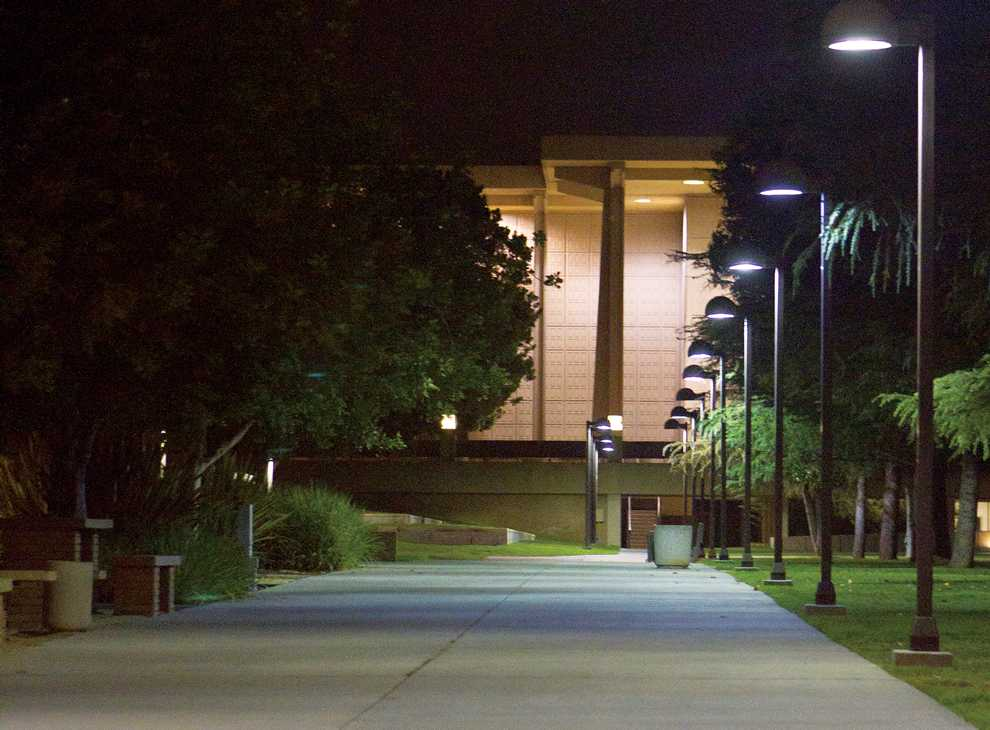 An empty pathway leading to the Oviatt Library is illuminated by dim lights lining the lawn. Photo Credit: Kat Russell / Daily Sundial