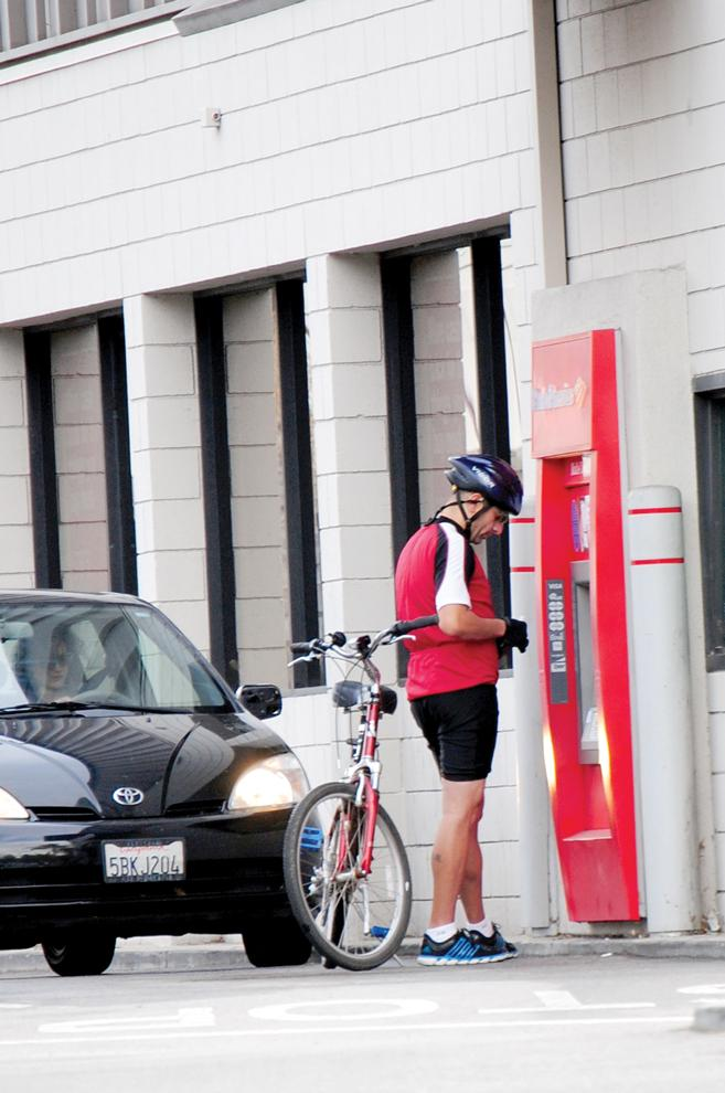 A bicyclist uses the Bank of America drive-through ATM machine. Bank of America has recently decided to not charge $5 a month to customers who use their debit cards that would have started in 2012. Photo Credit: Andres Aguila / Daily Sundial