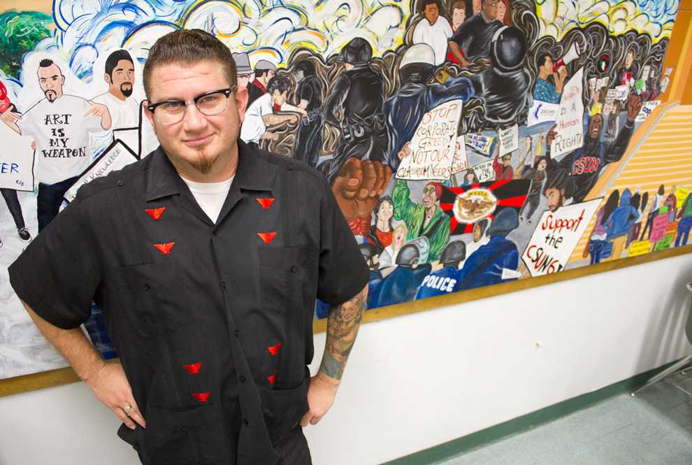 Jake+Prendez%2C+35-year-old+Chicana%2Fo+studies+graduate+student%2C+stands+alongside+a+mural+he+contributed+to+in+Jerome+Richfield+Hall+room+130.+Photo+Credit%3A+Tessie+Navarro+%2F+Visual+Editor