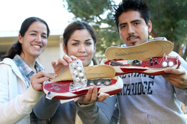 Melissa Martinez, senior civil engineering major, Ana Avelar, senior engineering major, and Eliud Munguia, senior computer science major, hold up their 'Powered Footwear' prototype which won second place at the Society of Hispanic Engineers conference in Anaheim in October. Photo Credit: Tessie Navarro / Visual Editor