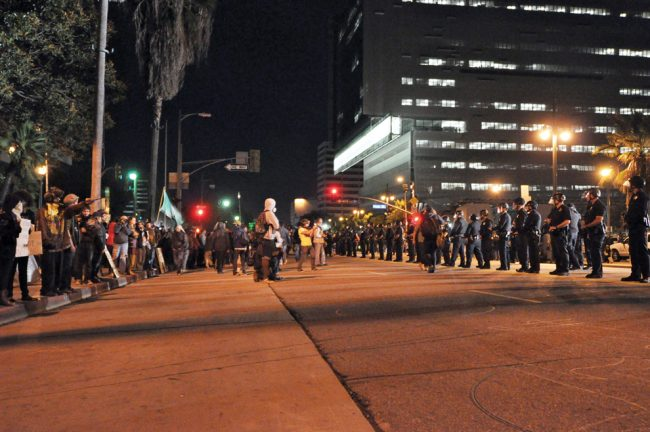 Protestors and police face-off on First Street at nearly 5:00 a.m. Monday. Polie promise they would not make arrests inside the camp, requesting protestors clear the streets. Photo Credit: Ken Scarboro / Editor in chief