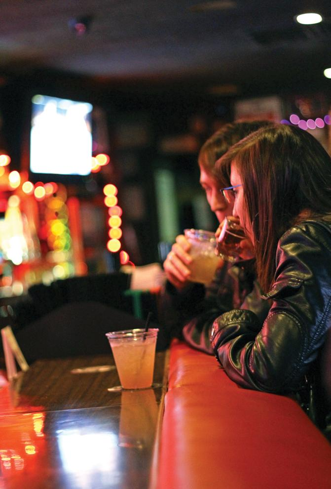 Two friends share drinks at the bar at the Stovepiper Lounge in Northridge, which is open seven days a week. Photo Credit: Charlie Kaijo / Daily Sundial