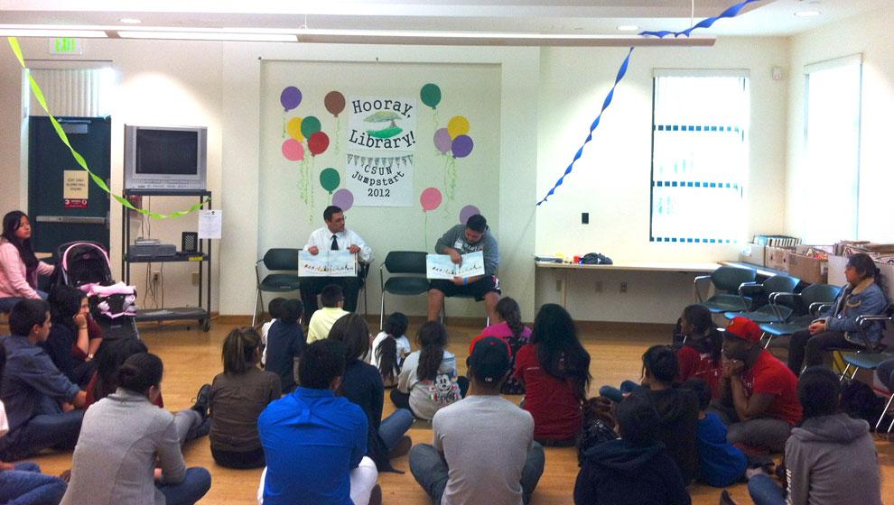 Jaime Rodriguez (left) and Jumpstart team leader William Valverde (right) read to a group of students. Photo courtesy of Rhea Triñaens