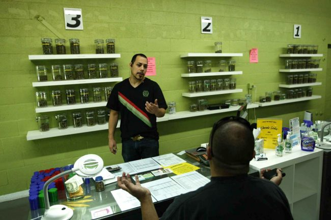 Budtender Cruz Juarez, 28, facing camera, prepares to fill an order for a patient at a medical marijuana dispensary in Long Beach, California, March 21, 2012. Photo courtesy of MCT