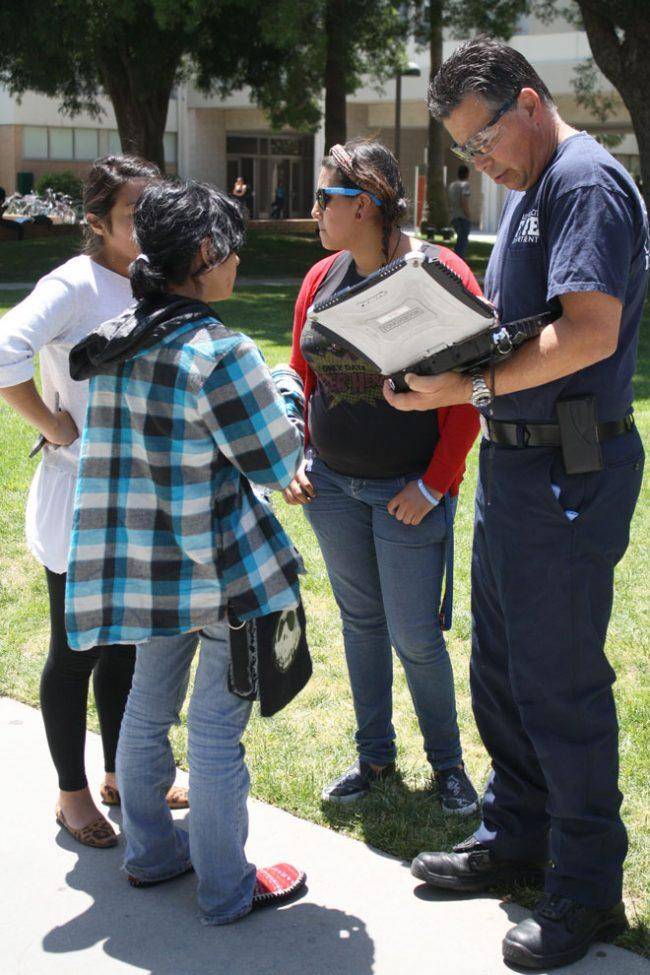 Raiza Arias, 18, double-major in theater and anthropology, gives her information to an officer after collapsing on Monday. Arias is one of the CSUN students who is currently on a hunger strike. Photo credit: Mariela Molina / Photo Editor