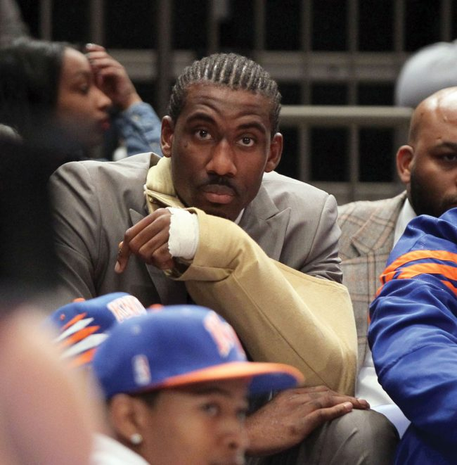 An injured Amare Stoudemire of the New York Knicks looks from the bench during Game 3 against Miami Thursday. Stoudemire injured himself punching a fire extinguisher after Game 2 and later said he did it because he