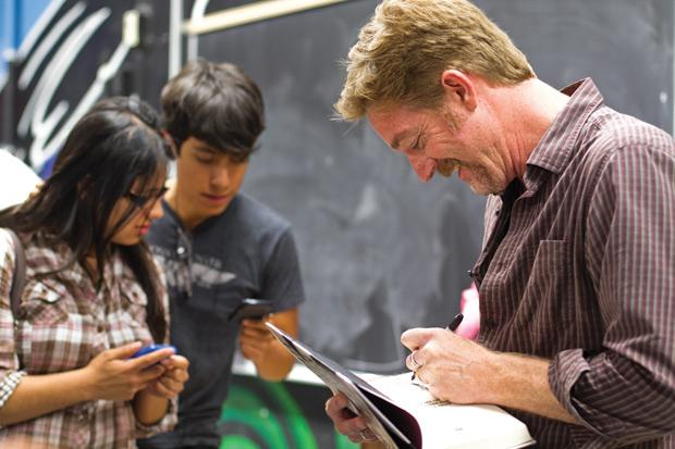 Jeff Biggers, author of 'State Out of the Union,' signs copy of his book for students and faculty, Tuesday at the Chicano/a studies department. Biggers' new book explores the contentious civil rights conflicts of Arizona's controversial SB1070 law and the banning of Chicano studies at public schools. Photo credit: Charlie Kaijo / Assistant Photo Editor
