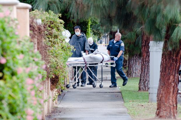 A dead body is carried out of a Grananda Hills residence by county coroners, Sunday. Four bodies were found in the 17400 block of Devonshire St. after police received a call about shots fired.