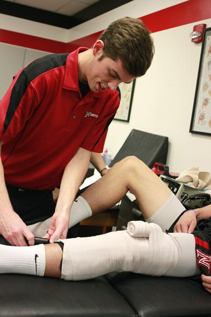 Max Haglun, 23, a kinesiology major studying athletic training, assists Stephen Hicks, 20, of the basketball team at the Athletic Training Center. Photo credit: Luis Rivas / Senior Reporter