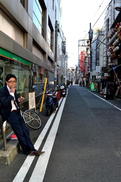 A Japanese business man takes a cigarette break beside a convenience market in Asakusa, Tokyo. Cigarette and beer vending machines are found around many corners in crowded areas in the city. Photo credit: John Saringo-Rodriguez / Daily Sundial