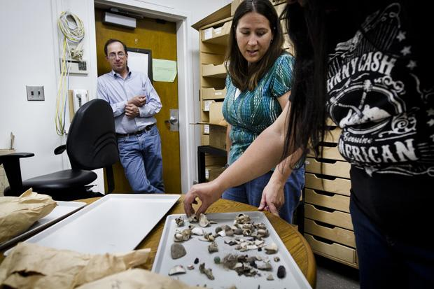 Ann Stansell (center), a second-year anthropology student, lay out artifacts collected from an excavation in Ventura County for indexing. Stansell said even something like a nail can help you date things. These items speak of the individuals who lived there. Photo credit: Charlie Kaijo / Senior Photographer