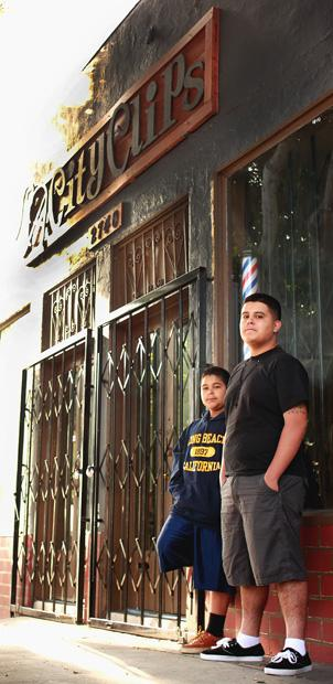 (From left) Rene Escapiti, 11, a sixth grader at El Sereno Middle School and his older brother Richard Lepe, 17, who is a senior at Woodrow Wilson High School, wait in front of LA City Clips, a barber shop in Boyle Heights, to open on March 25. Photo credit: Luis Rivas / Senior Reporter