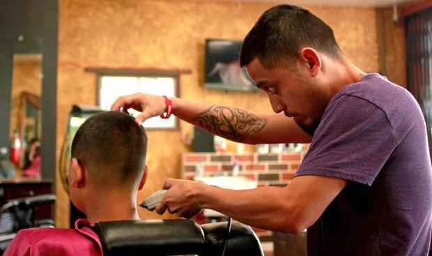 Romo gives a customer a buzz cut fade at his barber shop. Photo credit: Luis Rivas / Senior Reporter