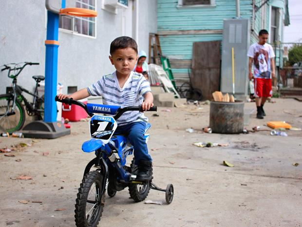 Antwan, 6, son of Alonso Romo, rides his bike at his family's backyard. Photo credit: Luis Rivas / Senior Reporter