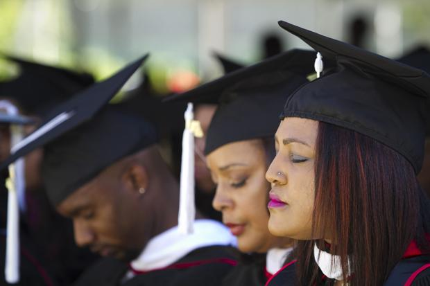 CSUN graduates receiving their master's degree bow their heads for a prayer during the Black graduation ceremony held at the lawn behind Manzanita Hall, Sunday. Charlie Kaijo/Senior Staff
