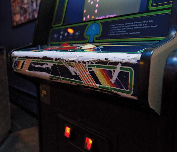 Often arcade cabinets show signs of quite a bit of wear. They've been used and abused over the years though they wear their battle scars well. This Centipede machine had putty spackled all over the control deck to fix a crack in the plexiglass that would normally protect the paper art underneath. Photo credit by Nathan McMahon/Opinion Editor