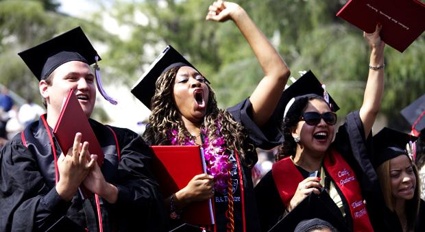 CSUN graduates celebrate getting their diplomas during the Art, Media and Communications graduation held at the Oviatt Library lawn, Wednesday. Photo credit: Loren Townsley / Editor in Chief