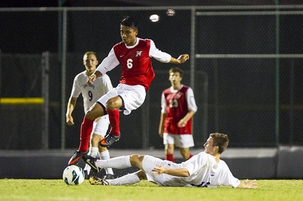 Senior Midfielder Carlos Benavides evades a sliding Albany defender. Photo credit: David Hawkins