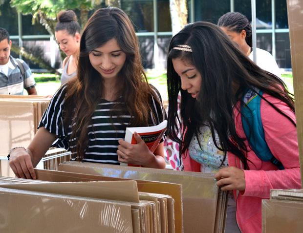 "Stephanie Sanchez (Left),18, a liberal studies major, and her friend Julie Flores, 17, a kinesiology, explore the ""Accent Design"" poster booth located outside Bayramian Hall at the Matador Mall, Monday. Photo credit: Victoria Becerril / Daily Sundial"