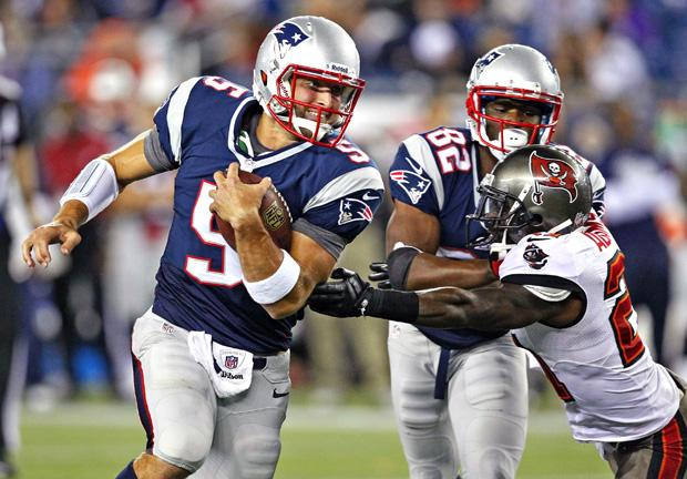 Former New England Patriots quarterback Tim Tebow eludes a Tampa Bay Bucaneers defender in a recent preseason game. Photo courtesy of MCT